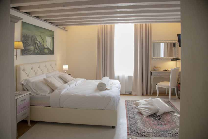 beautiful authentic venetian villa of 16th century interior design of a bedroom with carpet with exposed beams